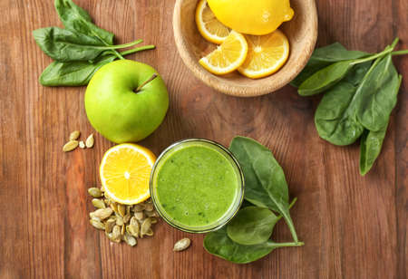 Glass of spinach smoothie on wooden background