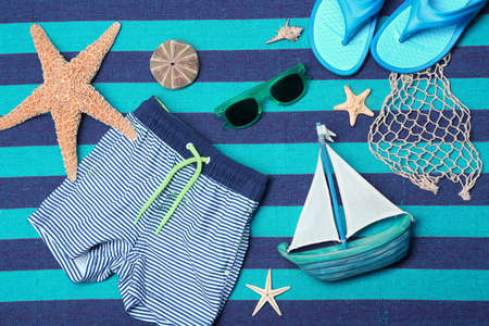 Composition with swimming trunks and sunglasses on color background