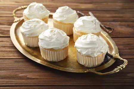 Tasty vanilla cupcakes on metal tray