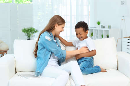 Happy mother with adopted African-American boy sitting on couch at home Stock Photo