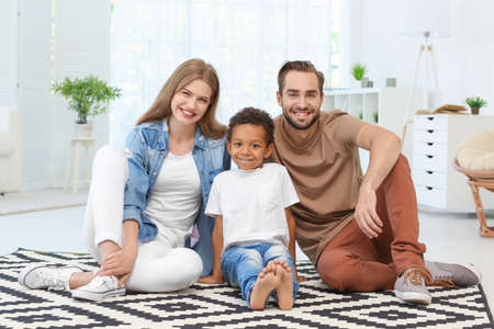 Happy couple with adopted African-American boy sitting on carpet at home Stock Photo