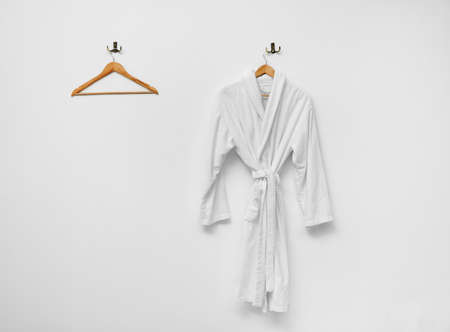 Bathrobe hanging on white wall