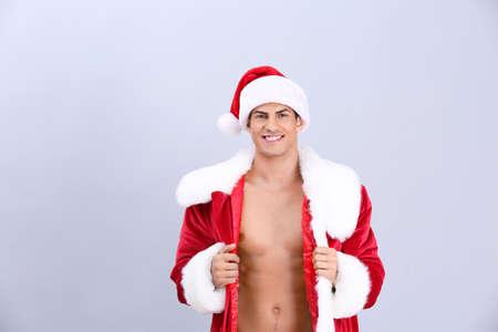 Handsome man in Santa costume on light background