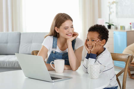 Happy mother with adopted African-American boy sitting at table in living room