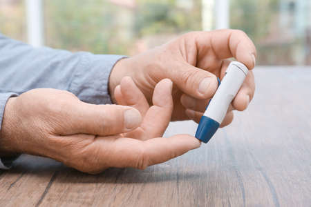 Man taking blood sample with lancet pen indoors Stock Photo