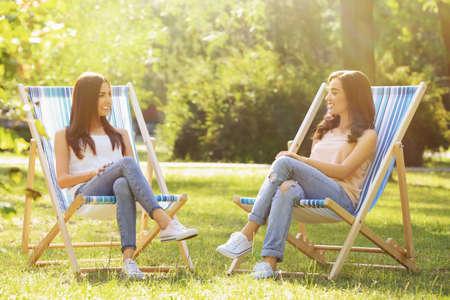 Beautiful young women sunbathing in park Stock Photo
