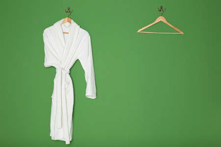 White bathrobe with wooden hangers on green background