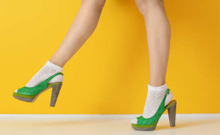 9563768728a Female legs in green high heel shoes and socks on color background