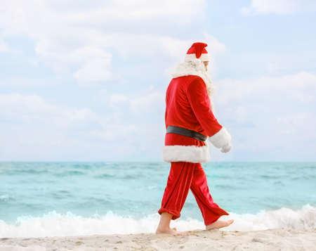 Authentic Santa Claus walking on beach
