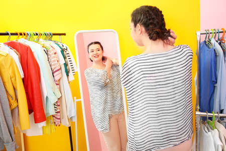 Beautiful overweight woman near mirror and rack with clothes at store Stock Photo