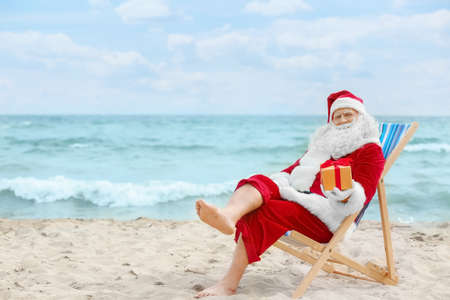 Authentic Santa Claus with gift box in deck chair on beach