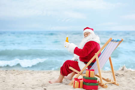 Authentic Santa Claus with bottle of drink relaxing in deck chair on beach