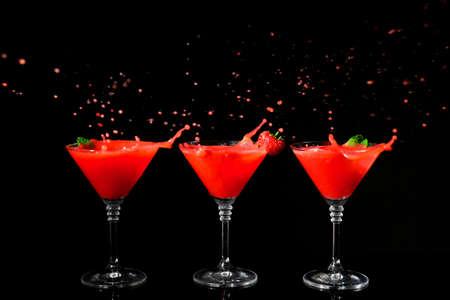 Glasses of delicious strawberry daiquiri with splash on black background