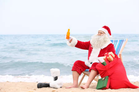 Authentic Santa Claus with bottle of drink and red bag relaxing on beach