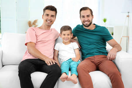 Male gay couple with foster son sitting on sofa at home. Adoption concept 写真素材