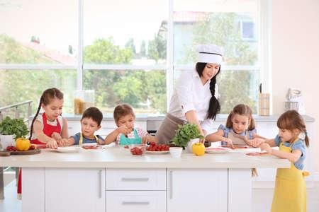 Grupo de niños y profesor en la cocina durante las clases de cocina.