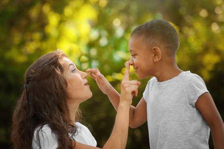 Junge Frau mit adoptiertem Afroamerikanerjungen draußen