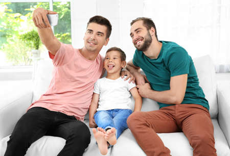 Male gay couple with foster son taking selfie. Adoption concept