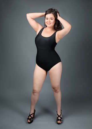 Beautiful overweight woman in black swimsuit on grey background