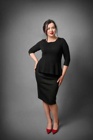 Beautiful overweight woman in black formal dress on grey background