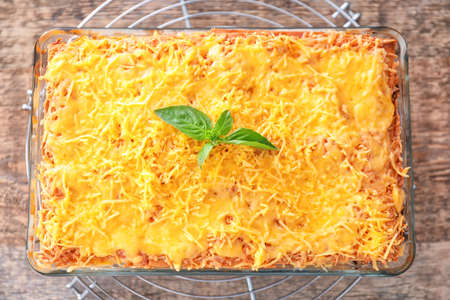 Traditional meat lasagna in baking dish on table