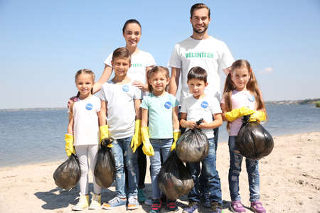 Young volunteers and children with garbage bags on beach