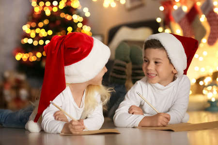 Cute kids writing letter to Santa in room decorated for Christmas