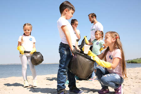 Young volunteers and children collecting garbage on beach Stock Photo