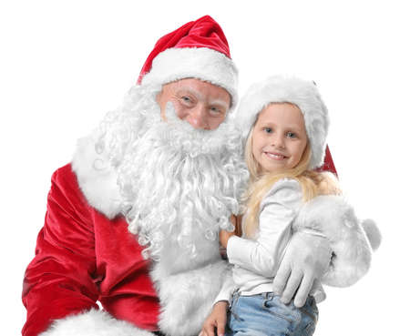 Cute little girl in Christmas hat sitting on Santa's lap against white background 免版税图像