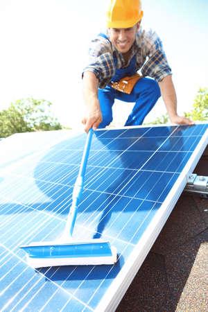 Worker cleaning solar panels after installation outdoors Reklamní fotografie