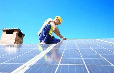 Trabajador instalando paneles solares al aire libre Foto de archivo