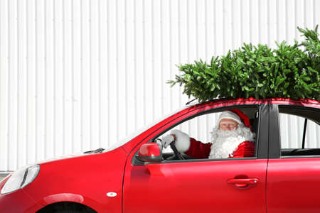 Authentic Santa Claus driving car with fir tree on it's top Stock Photo