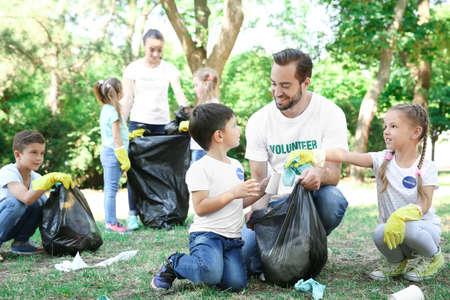 Jonge vrijwilligers en kinderen die afval in park verzamelen