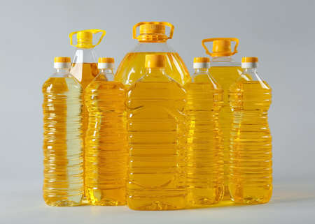 Bottles of cooking oil on light background