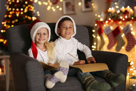 Cute kids with letters to Santa in room decorated for Christmas