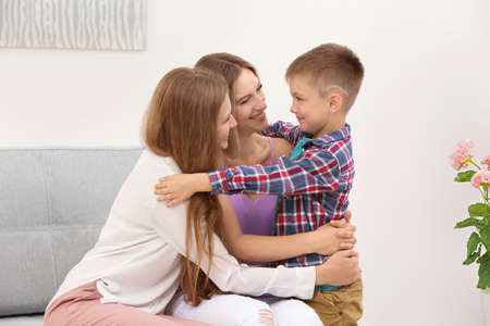 Female gay couple with foster son spending time at home. Adoption concept