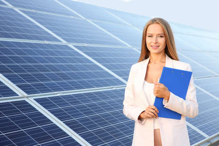 Beautiful young woman with clipboard standing near solar panels outdoors