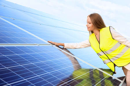 Beautiful young engineer standing near solar panels outdoors