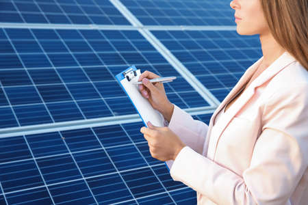 Female engineer developing project on installation of solar panels outdoors