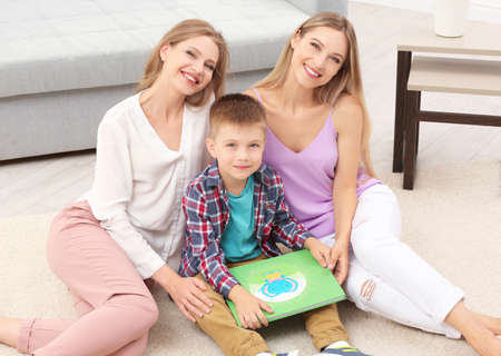 Lesbian couple reading with foster son at home. Adoption concept Standard-Bild