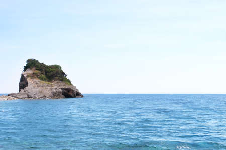View of blue sea with rocky island