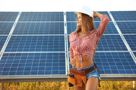 Beautiful young engineer on solar panels installation outdoors