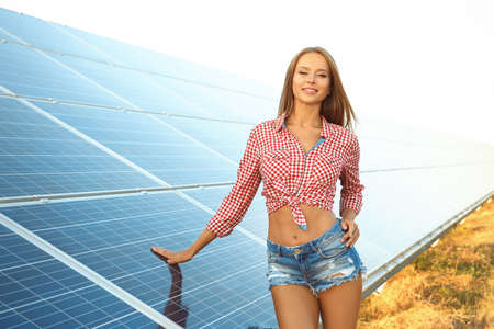 Beautiful young woman near solar panels outdoors Stockfoto