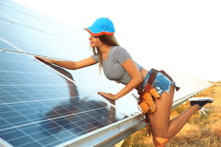 Beautiful young engineer near solar panels outdoors
