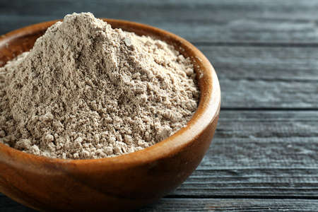 Superfood powder in bowl on wooden table