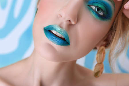 Young woman with bright green makeup on color background, closeup