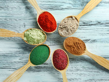 Different colorful superfood powders in spoons on wooden table Banco de Imagens