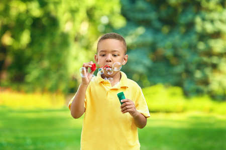 Cute African American boy blowing soap bubbles outdoors Archivio Fotografico