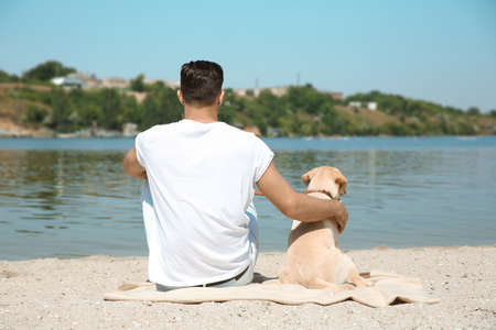 Young man resting with yellow retriever near river