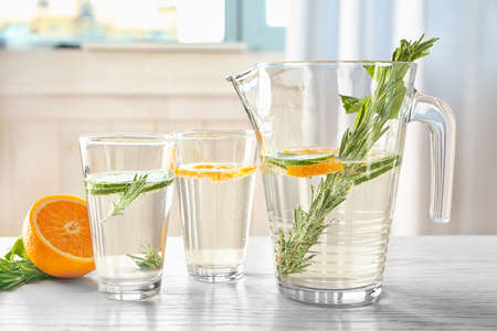 Glasses and jug with fresh rosemary drink on table
